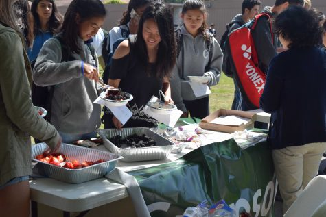 "Sophomore Samantha Kao, left, grabs a healthy snack. Parent volunteers served locally grown fruit and granola during Day 1 of Change in Our Schools week,    which focuses on issues that need change at Palo Alto High School. """"Change in Our Schools Week is something that the School Wellness and Climate Committee has been working on that is basically a whole week long full of events during lunch time that focus on changes in our school, like bringing more awareness to certain events or certain things that we would like to focus on more as a school,"" junior Noor Navaid said."