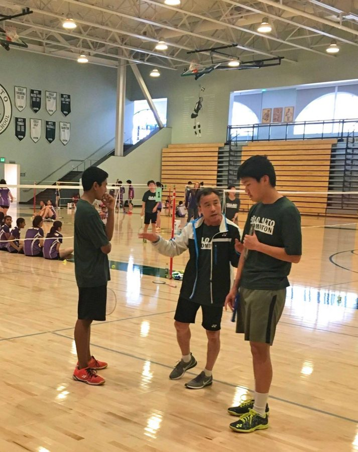 Junior Zakir Ahmad and sophomore Jeffrey Mi strategize with Coach Kenny Chung in between the first and the second badminton game. Mi said the coach told them to try and move the other team around more.
