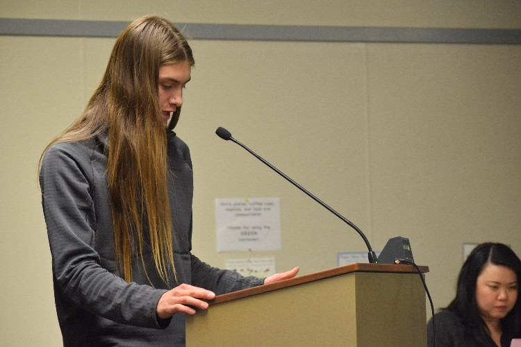 Junior Galileo Defendi-Cho reads a statement in support of building solar panels in Palo Alto High School's El Camino parking lot at a school board meeting on Tuesday, May 24. The board passed a proposal that removed two proposed solar panels in the El Camino parking lot.