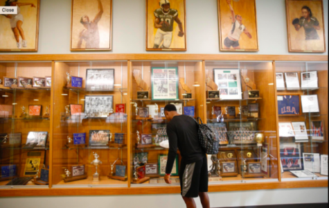 "Paly alumnus KeeSean Johnson ('14) visits the Peery Family Center at Palo Alto High School where a portrait of Davante Adams, a mentor of Johnson's, as well as a Paly alumnus who now plays for the Green Bay Packers, is displayed. Johnson was picked by the  Arizona Cardinals in the sixth round of the 2019 NFL draft. Former coach Jason Fung described Johnson as a ""hard-working kid, always had dreams and aspirations to play football."" Photo provided by: Fresno State fundraising department"