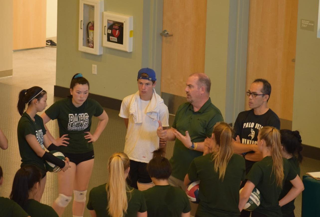 Coach Chris Crader talks to the girls' volleyball team during practice. Crader is the new volleyball coach and is getting ready for the season.