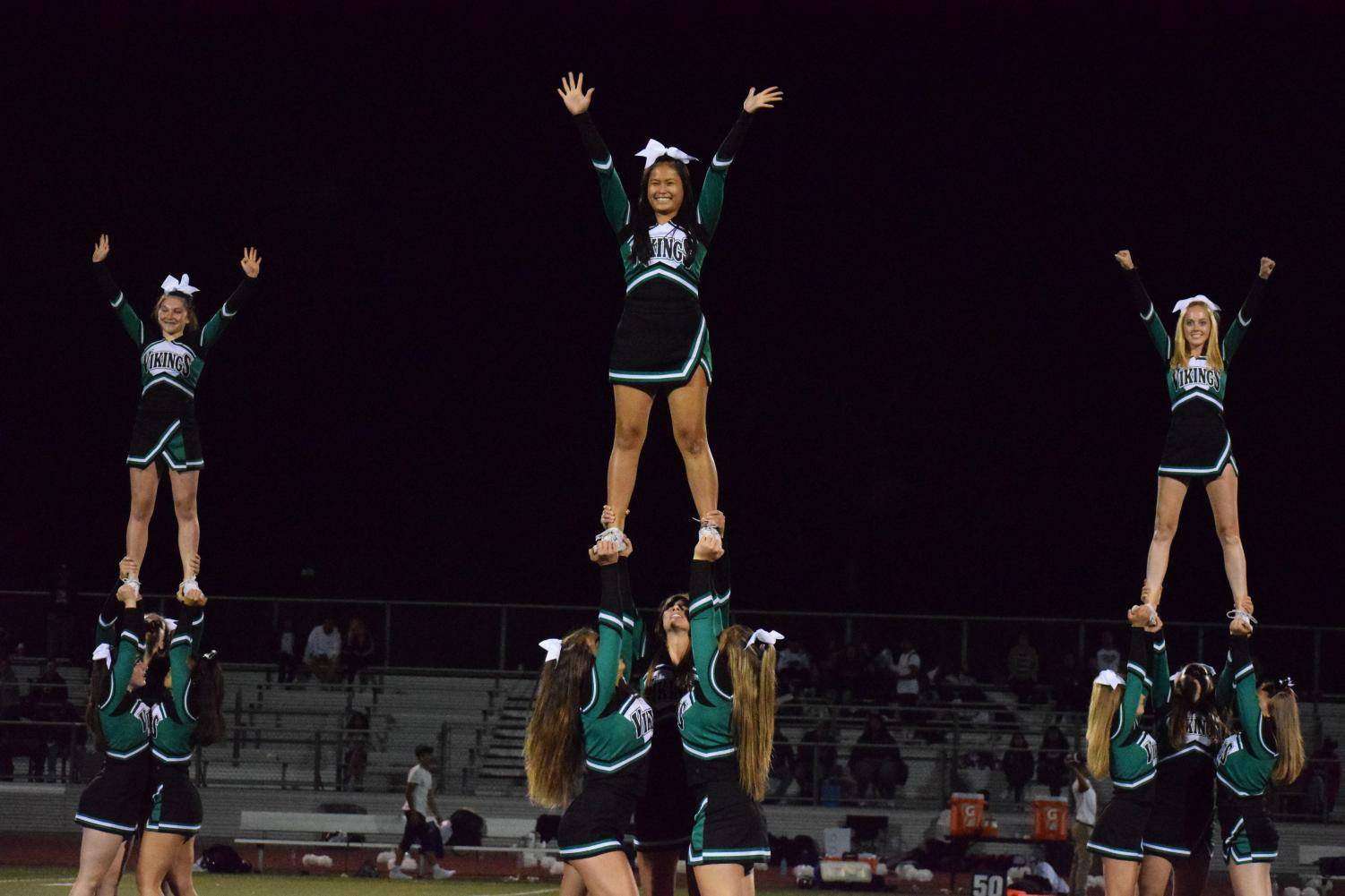 """The Palo Alto High School varsity cheer team performs at a football game in September of 2019. The team will participate in the United Spirit Association national competition Feb 14 to Feb 16 after qualifying in Oct. """"My expectations for my team in nationals is that we bring everything to the mat and have no regrets,"""" senior captain Tati Taylor stated over text message. """"All of our hard work is paying off!"""" Photo: Amy Yu"""