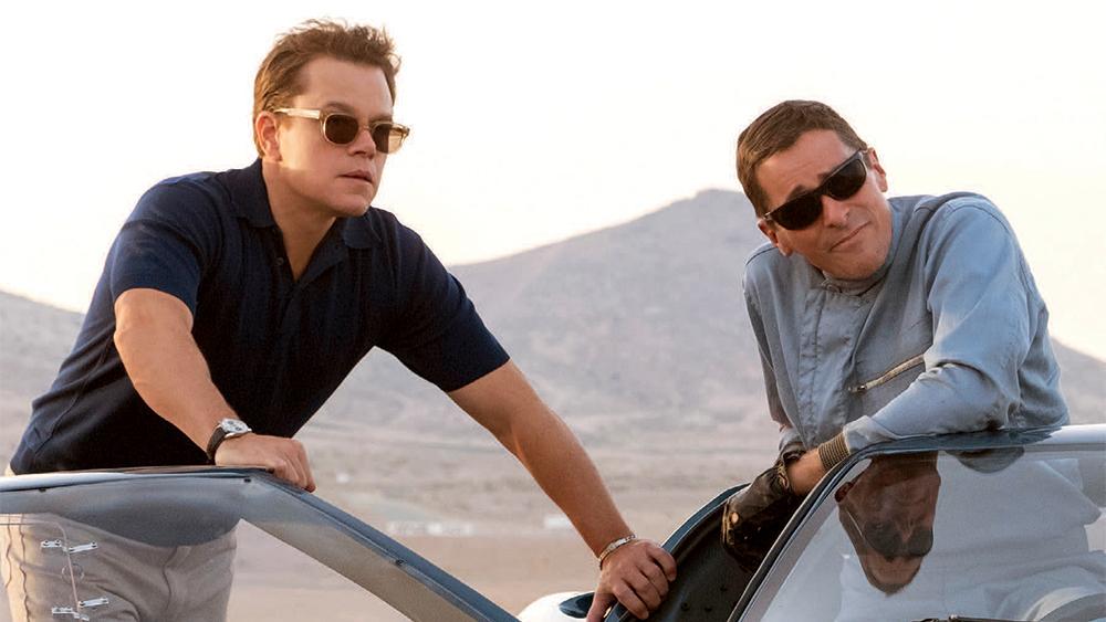 """Carrol Shelby (Matt Damon, left) talks to Ken Miles (Christian Bale, right) leaning on a GT40. The film, """"Ford v. Ferrari"""