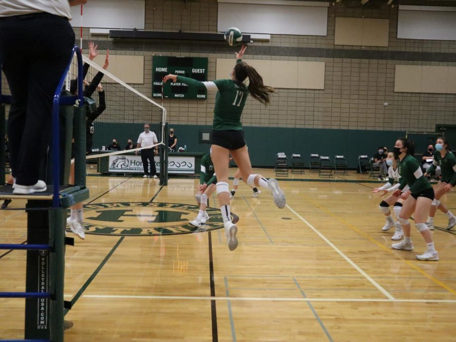 Junior outside hitter Amelia Vugrincic tips the ball over the net during Paly
