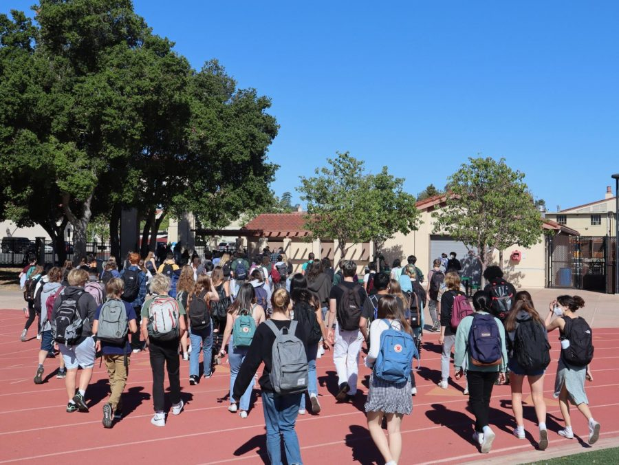 """Palo Alto High School students evacuate their classrooms and head towards the football field after a fire alarm on Wednesday morning. [[ABCD caption missing """"B"""" for background]] Junior Giada Parigi reported that the volume of the fire alarm caused an atmosphere of confusion. """"It [the fire alarm] seemed much louder than it has been in the past, so no one could really hear what was going on,"""" she said. Photo: Daniel Garepis-Holland."""