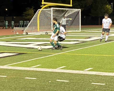 Paly senior Christopher Chen shields the ball from his defender by the Spartans