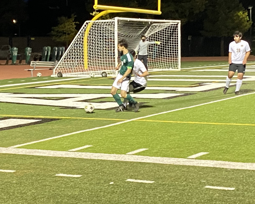 Paly senior Christopher Chen shields the ball from his defender by the Spartans' goal during the Vikings' home game on Friday against the Spartans. Despite their valiant efforts, the Vikings ended the game with a tie. However, according to coach Rusty Millard, the team's performance was a noticeable improvement compared to past games.