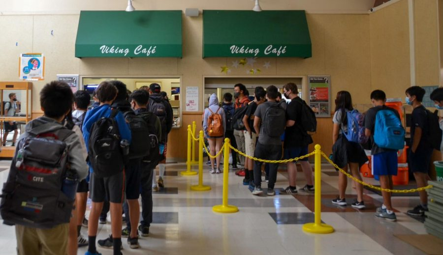 """Students line up to receive free lunch from the cafeteria in the Student Center at Palo Alto High School. The Palo Alto Unified School District has been offering lunch for free to students due to a requirement from the state government. Freshman Divij Motwani, who eats free lunch on a daily basis, said the option helps those in need. """"It [free lunch] wouldnt really have changed [things] to me, but I think its good for everyone else, especially because theres some people who cant afford lunch,"""" Motwani said. (Photo: Neil Rathi)"""
